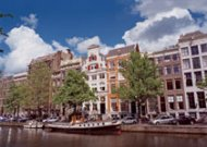 Discover houses and boats along a canal in Amsterdam